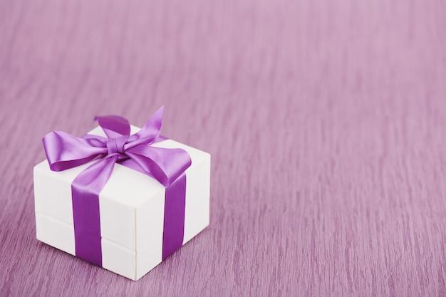 Geschenkdoos met paarse strik op roze oppervlak