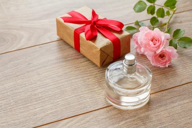 Geschenkdoos met parfum op houten planken versierd met roze roze bloemen. bovenaanzicht.
