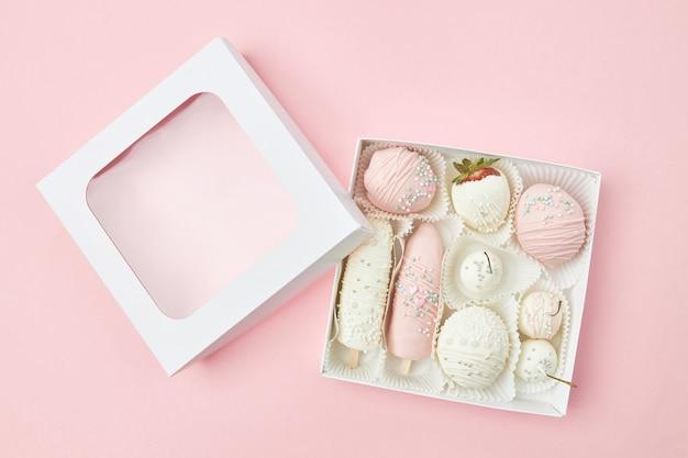 Geschenkdoos met rijp fruit bedekt met witte en roze chocolade ligt op een roze achtergrond
