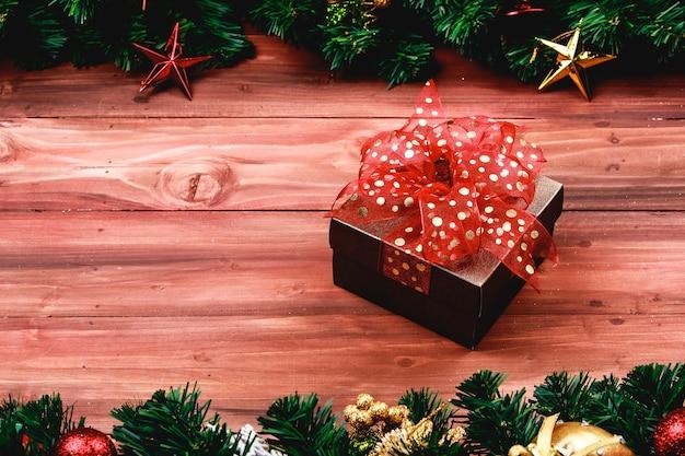 Geschenkdoos met rode kleur lint op hout achtergrond met kerstboom en traditionele ornamenten xmas rekwisieten met kopie ruimte. concept van gelukkig en vreugdevol in festival.