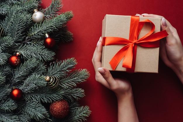 Geschenkdoos met rode strik en kerstboomtakken