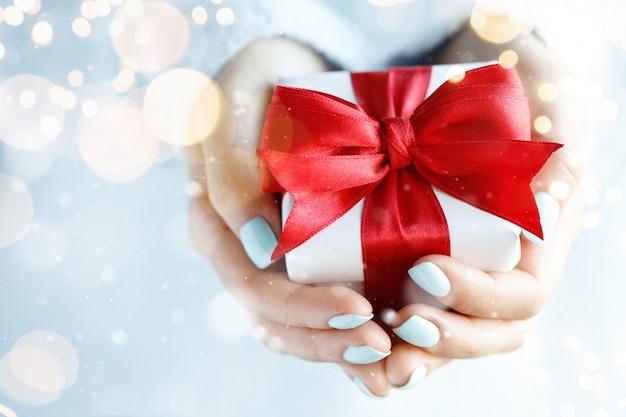 Geschenkdoos met rode strik in handen van de vrouw