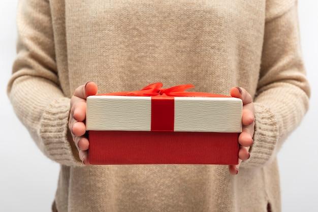 Geschenkdoos met rode strik in vrouwelijke handen