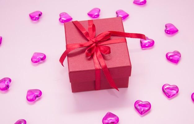 Geschenkdoos met rode strik, op een roze achtergrond. harten op een roze achtergrond