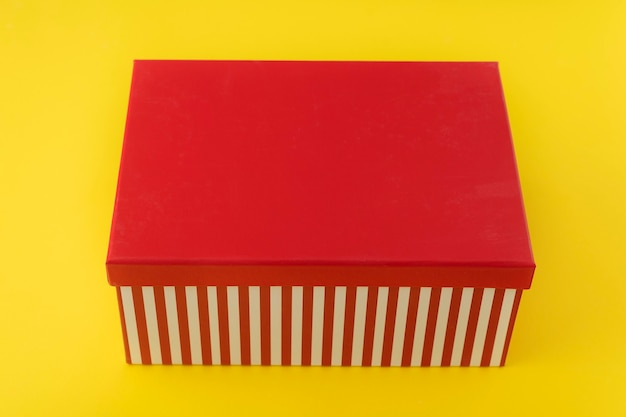 Geschenkdoos met rood deksel op gele achtergrond. kopieer ruimte. mockup.