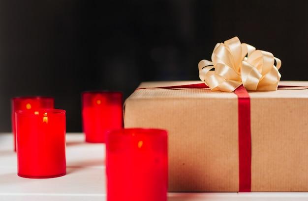 Geschenkdoos met rood lint en boog en kaarsen.