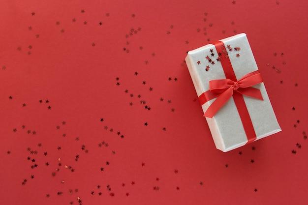 Geschenkdoos met rood lint en confetti decoraties op pastel papier kleurrijke achtergrond. plat leggen, bovenaanzicht, kopie ruimte