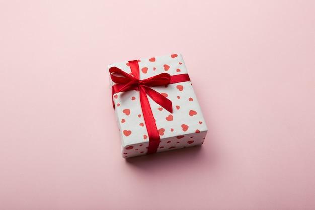 Geschenkdoos met rood lint en hart op koraal