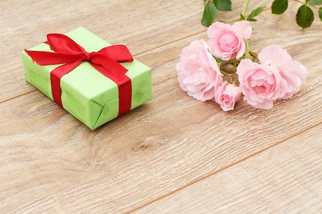Geschenkdoos met rood lint en mooie roze rozen op de houten planken. concept van het geven van een geschenk op vakantie. bovenaanzicht.