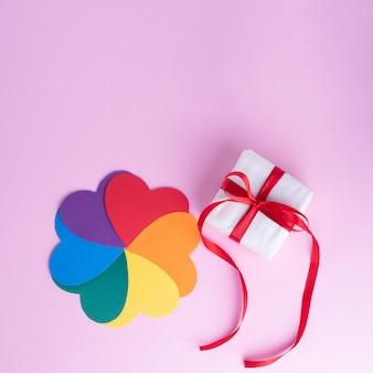 Geschenkdoos met rood lint en veelkleurige bloemvorm met regenboogbloemblaadjes op een roze oppervlak, kopie ruimte, vierkant frame. lgbt-concept