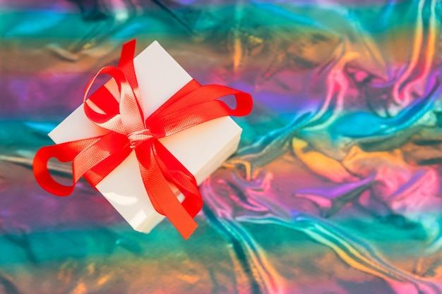 Geschenkdoos met rood lint, glittery kleurrijke background.magical kerstcadeau doos omwikkeld met