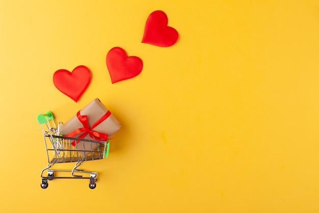 Geschenkdoos met rood lint in mini kruidenierswinkelwagentje, rode harten op gele muur, verkoop en liefdeconcept, valentijnsdag, exemplaarruimte, horizontaal