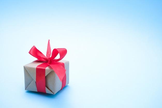 Geschenkdoos met rood lint op blauw.