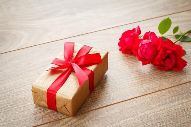 Geschenkdoos met rood lint op houten planken met rood roze bloemen. bovenaanzicht.