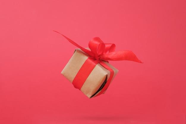 Geschenkdoos met rood lint op rood.