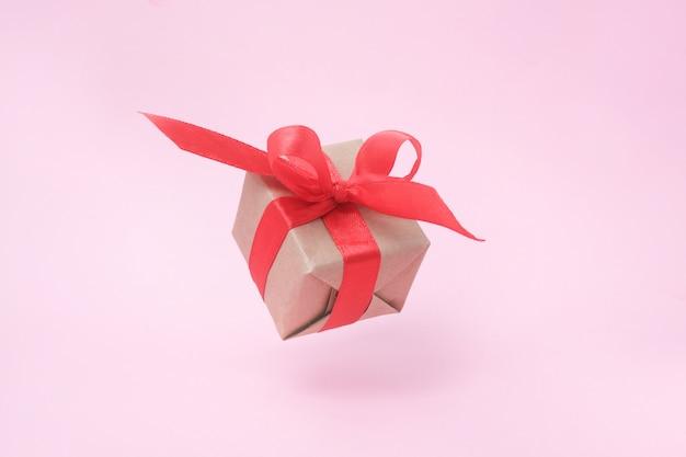 Geschenkdoos met rood lint op roze.