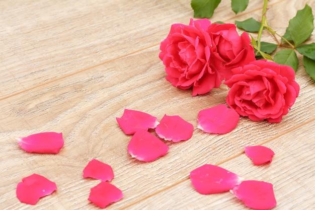 Geschenkdoos met rood lint, rozenblaadjes en mooie roze rozen op de houten achtergrond. concept van het geven van een geschenk op vakantie. bovenaanzicht.