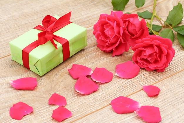 Geschenkdoos met rood lint, rozenblaadjes en mooie rozen op de houten achtergrond. concept van het geven van een geschenk op vakantie. bovenaanzicht.