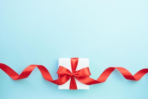 Geschenkdoos met rood lint strik op blauwe achtergrond. cadeau voor kerstmis, verjaardag of valentijnsdag. feestelijke decor achtergrond. bovenaanzicht plat met vrije ruimte.
