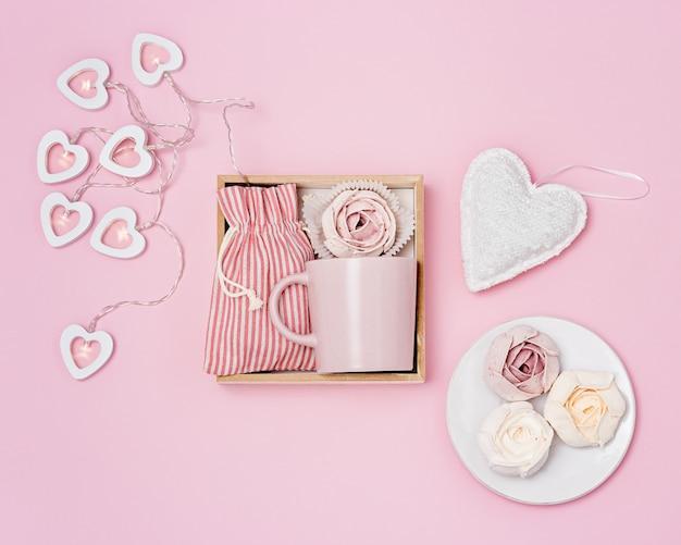 Geschenkdoos met roze mok, marshmallow en verrassing in stoffen zak, snoepverzorgingspakket versierd met slinger van harten