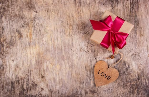Geschenkdoos met satijnen strik en houten hart op een oude houten achtergrond