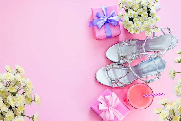 Geschenkdoos met satijnen strik voor vrouwen bloemen koop schoenen een glas cocktail.