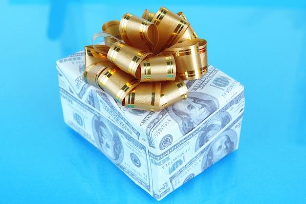 Geschenkdoos met strik bedekt dollars op blauwe achtergrond