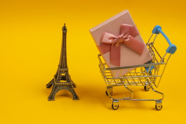 Geschenkdoos met strik, beeldje van de eiffeltoren, winkelwagentje op gele achtergrond. winkelen in parijs, souvenirs
