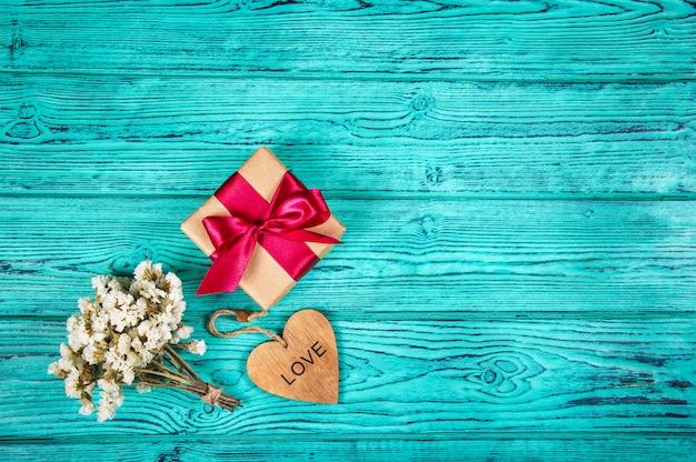 Geschenkdoos met strik en houten hart op een blauwe houten achtergrond. kopieer ruimte