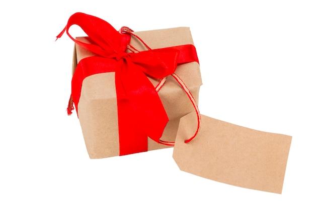 Geschenkdoos met tag met lege ruimte voor een tekst geïsoleerd op de witte achtergrond, inclusief uitknippad.