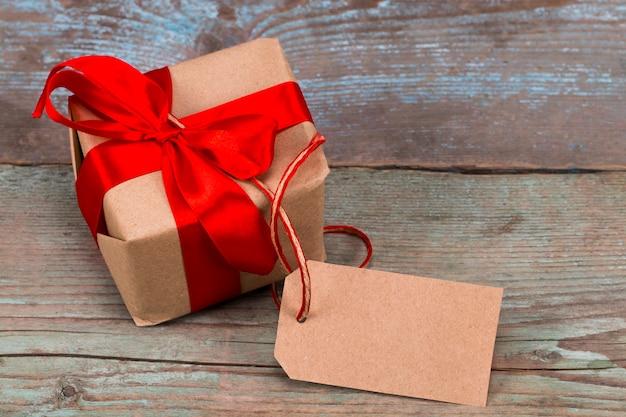 Geschenkdoos met tag met lege ruimte voor een tekst op houten achtergrond.