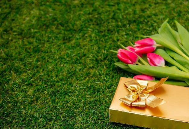 Geschenkdoos met tulpen op groen gras in een tuin