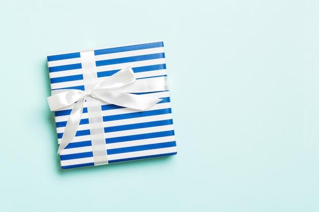 Geschenkdoos met witte strik voor kerstmis of nieuwjaarsdag op blauwe ondergrond, bovenaanzicht met kopie ruimte