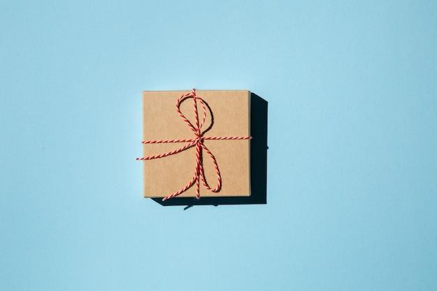 Geschenkdoos of cadeau verpakt in ambachtelijk papier op een blauwe achtergrond vakantiecadeau feestelijke achtergrond