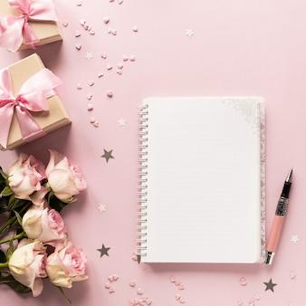 Geschenkdoos of geschenkdoos en bloemen op roze tafelblad weergave.