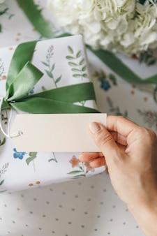 Geschenkdoos omwikkeld met papier met bloemenpatroon en een kaart