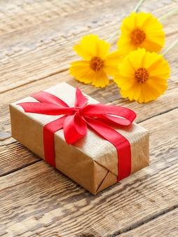 Geschenkdoos omwikkeld met rood lint en gele bloemen op oude houten planken. bovenaanzicht.