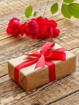 Geschenkdoos omwikkeld met rood lint op oude houten planken versierd met rode rozen. bovenaanzicht.