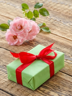 Geschenkdoos omwikkeld met rood lint op oude houten planken versierd met roze rozen. bovenaanzicht.