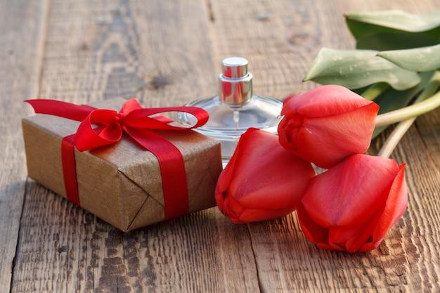 Geschenkdoos omwikkeld met rood lint, rode tulpen en fles parfum op houten planken.