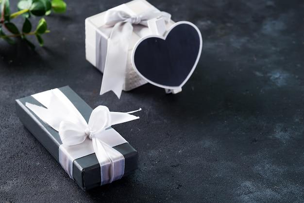 Geschenkdoos omwikkeld met wit satijnen lint op donkere steen. modern cadeau voor elke vakantie, kerst, valentijn of verjaardag