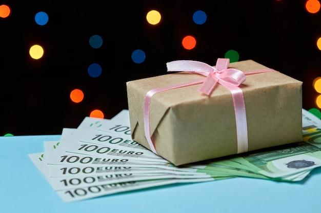 Geschenkdoos op biljetten van 100 euro tegen kleurrijke lichten