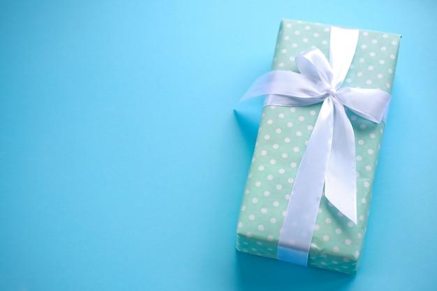 Geschenkdoos op blauwe achtergrond met wit lint