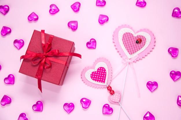 Geschenkdoos op een roze achtergrond. twee roze hartvormig. cadeau voor een meisje.