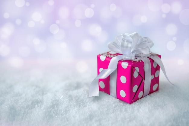 Geschenkdoos op sneeuw, op een zachte achtergrond met bokeh. feestelijke kerst- en nieuwjaarskaart vanuit kopie ruimte.
