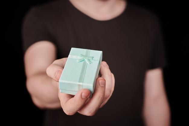 Geschenkdoos ter beschikking. valentijn cadeau. kleine jubileumgeschenkdoos van de mens. klein verrassingsconcept. zwarte achtergrond.