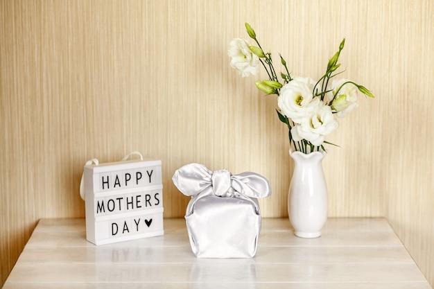 Geschenkdoos trendy verpakt in zijde stof in furoshiki techniek, lichtbak met belettering happy mother's day, witte bloemen eustoma of lisianthus in vaas op houten tafel. zero waste life concept.