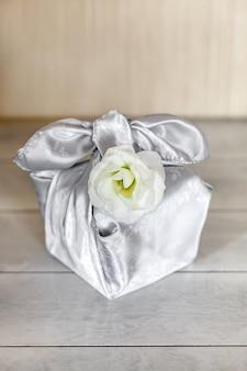 Geschenkdoos trendy verpakt in zijde stof in furoshiki techniek, witte bloem eustoma of lisianthus, houten tafel. zero waste life concept.