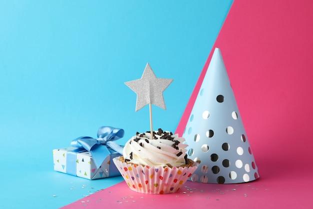 Geschenkdoos, verjaardagshoed en cupcake op tweekleurige achtergrond, ruimte voor tekst