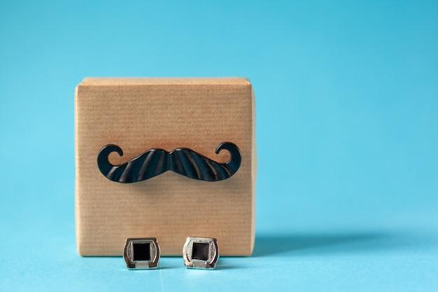 Geschenkdoos verpakt in ambachtelijk papier met snor en manchetknopen